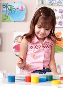 Child preschooler painting in classroom. Child care.