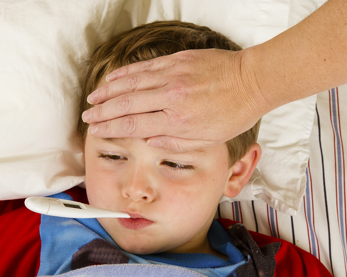 Sick child boy being checked for fever and illness while resting